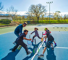 Kids on tennis court with an instructor practicing