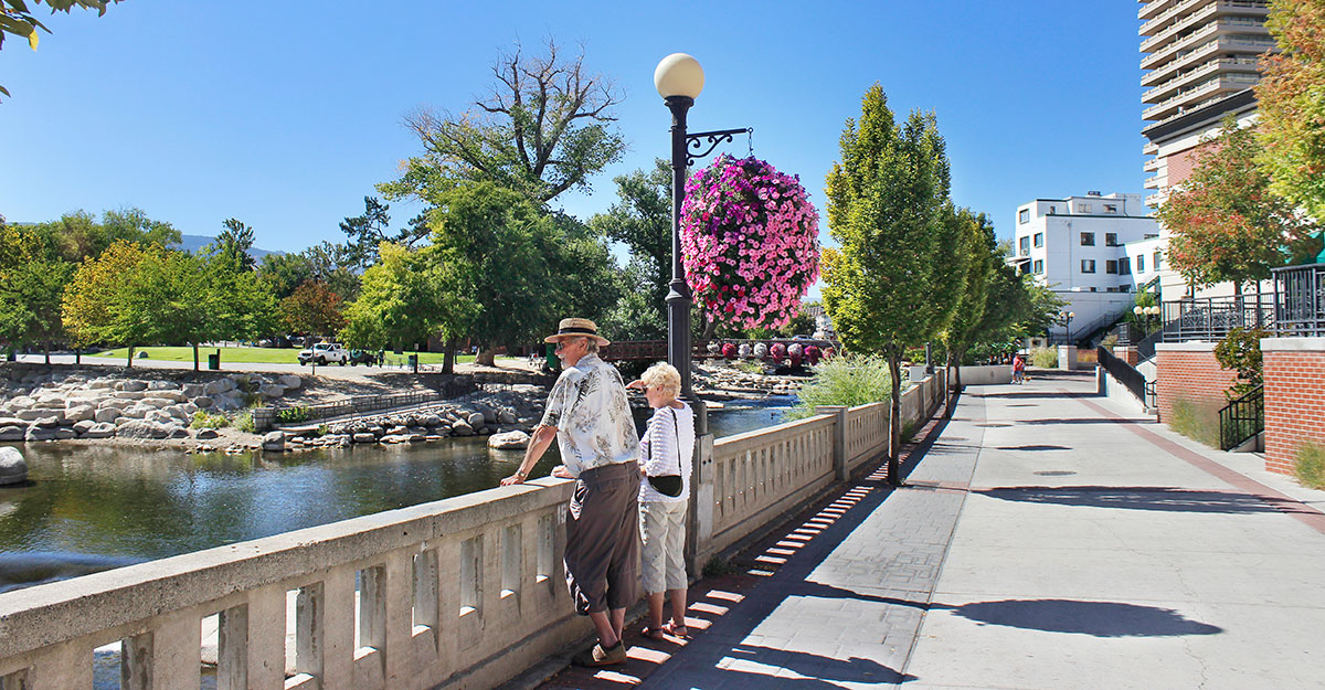 Older couple along riverwalk looking at Truckee River