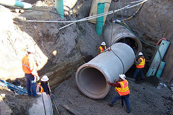 People working on sewer pipes