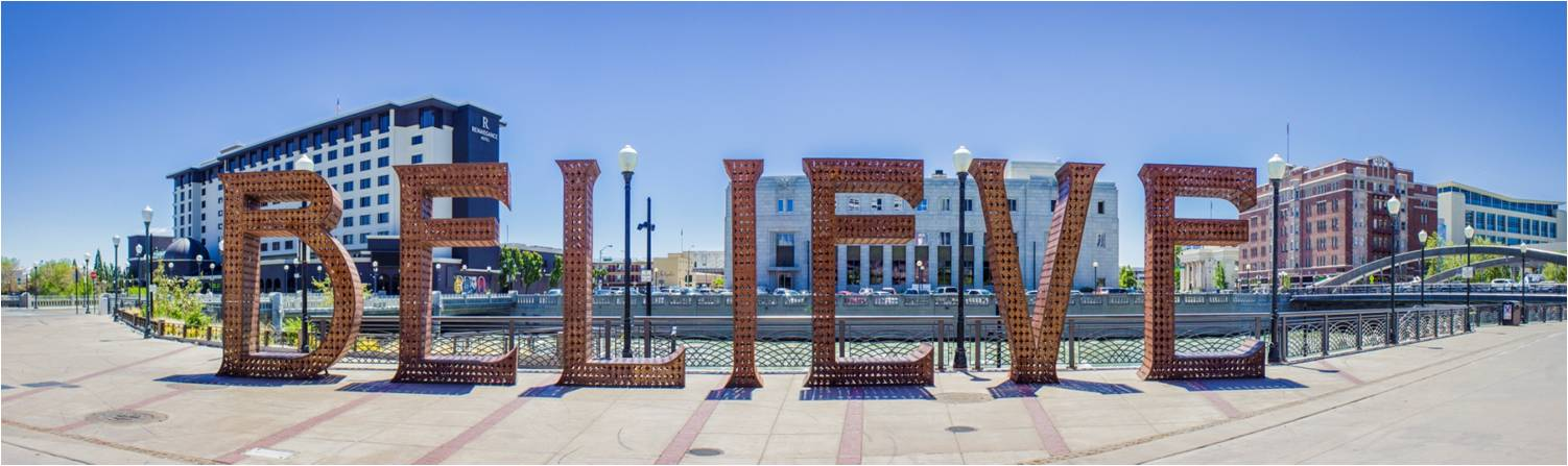 Panoramic image of plaza with large sculptural letters that spell out BELIEVE against the backdrop of buildings
