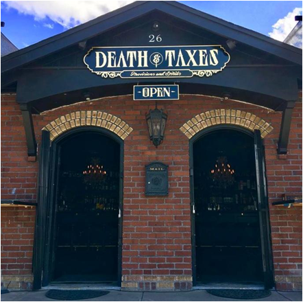 Historic Brick Building at 26 Cheney St. with sign above entrance that reads Death and Taxes