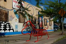 bike rack shaped like a weiner dog on a city sidewalk with colorful building behind