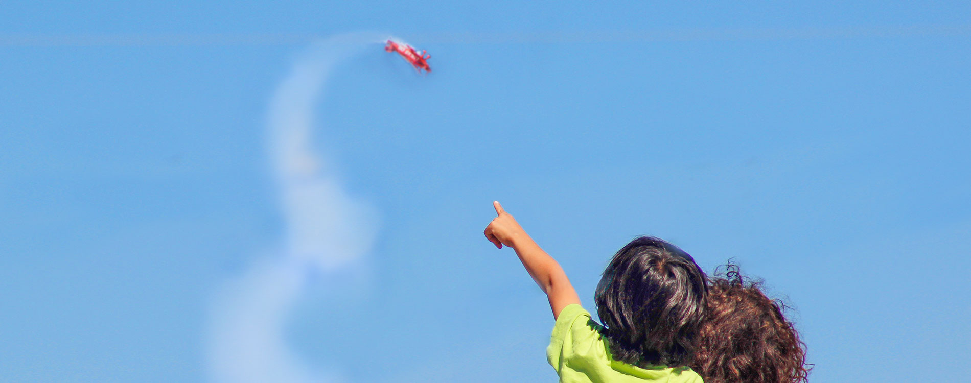 Two kids pointing to a plane in the sky